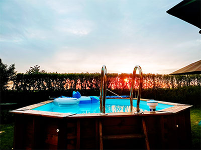 A portable above ground pool with a ladder. This one has a wooden outside finish.