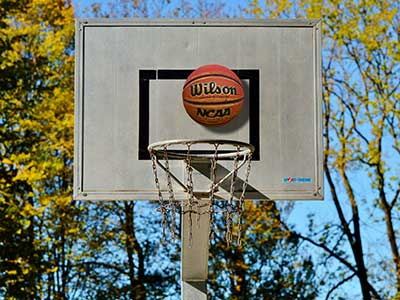 Basketball hoop with backboard and a ball that's about to go in. I love how this is so easy to put up in the backyard and children and adults can easily play with it.