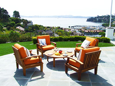 Rattan furniture for an outdoor patio. 4 Rattan seats with orange cushions and a round table.