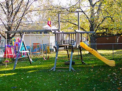 """A big swing set that includes a slide, swings and a """"tower"""""""