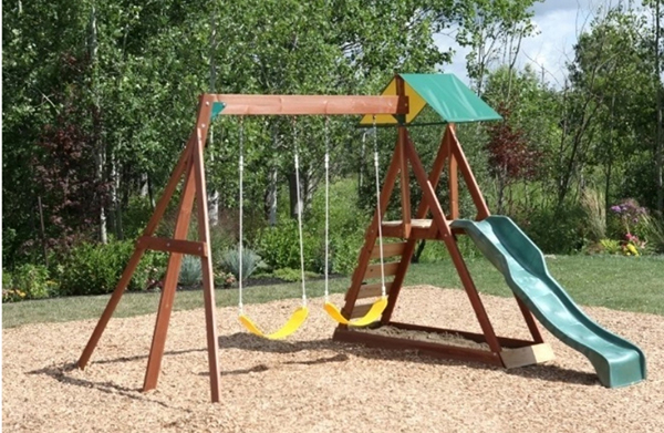 A smal playset with  two swings, a rock wall and ladder combo, a slide and a bottomless sandpit.